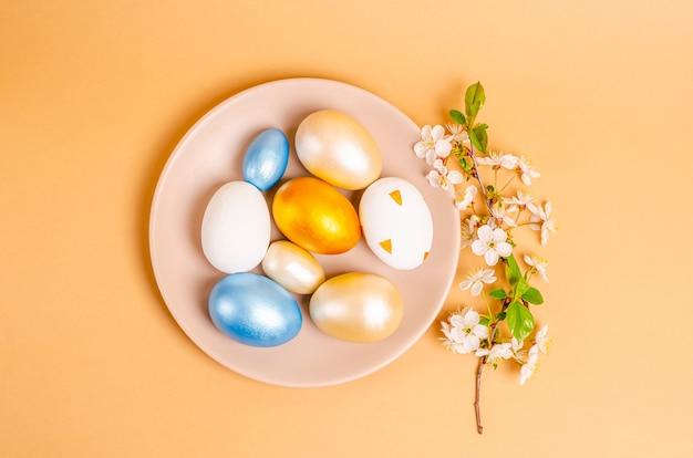 Uova colorate per pasqua su un piatto con rami di ciliegio in fiore su fondo beige. concetto di stagionalità, primavera, cartolina, vacanza. lay piatto, posto per il testo. vista dall'alto.