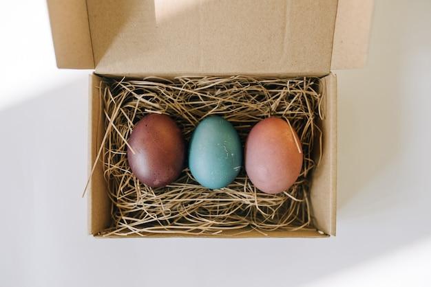 Uova colorate su paglia in una scatola