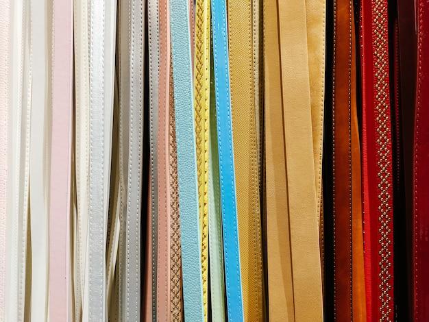 Cinture in pelle colorata, primo piano, sfondo, trama. cinture colorate per borse o collari per cani. molte diverse linee verticali, sfondo astratto.