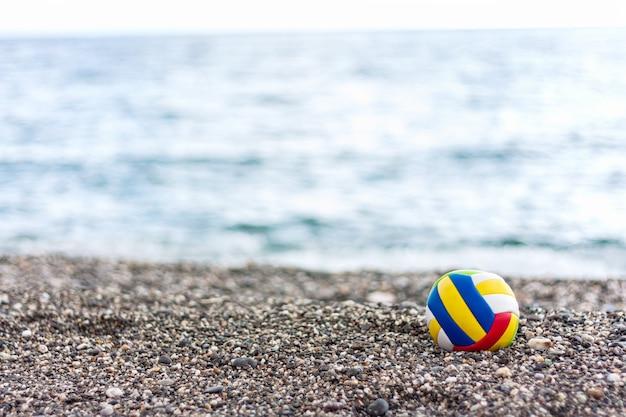 Palla colorata per bambini solitari su una spiaggia di ghiaia sul fondo del mare estivo.