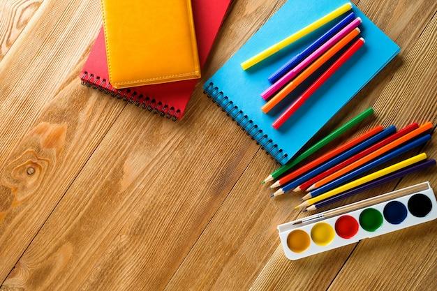 Pennarelli e matite colorate, un blocco da disegno pulito, acquerelli su un tavolo di legno. materie di creatività dei bambini, scuola e istruzione prescolare.
