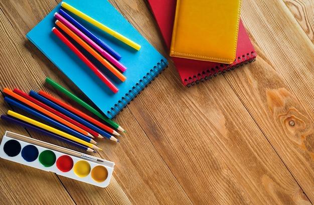 Pennarelli e matite colorate, un blocco da disegno pulito e acquerelli su un fondo di legno