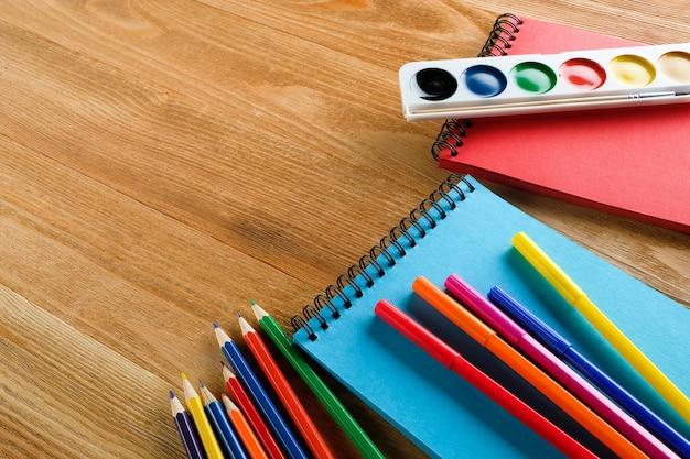 Pennarelli e matite colorate, un blocco da disegno pulito e acquerelli su un tavolo di legno.