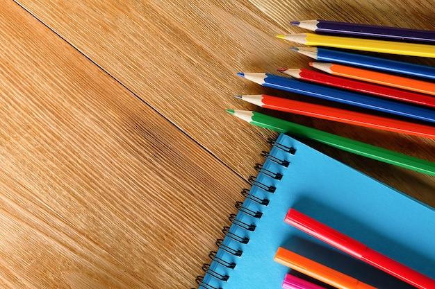 Pennarelli e matite colorate, un blocco da disegno pulito, su un fondo di legno