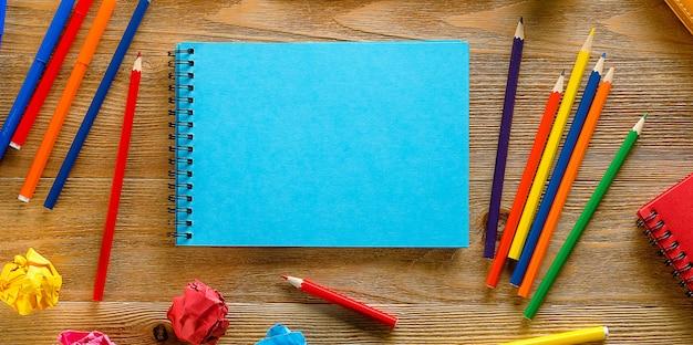 Pennarelli e matite colorate, un blocco da disegno pulito, su un tavolo di legno. materie della creatività dei bambini, istruzione scolastica e prescolare. banner.