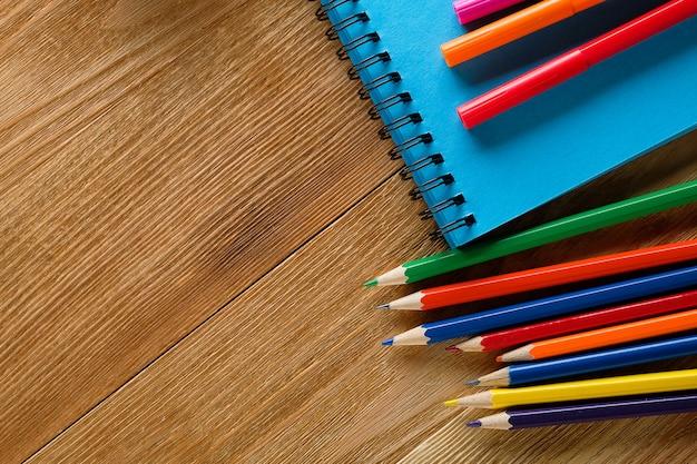 Pennarelli e matite colorate, un blocco da disegno pulito, su un tavolo di legno.
