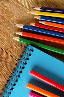 Indicatori e matite colorati, un blocco da disegno pulito, sulla tavola di legno.