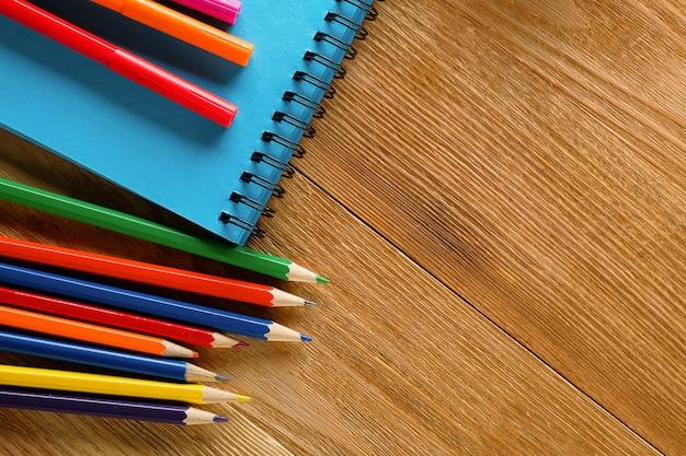 Indicatori, matite e blocco note colorati su una tavola di legno.