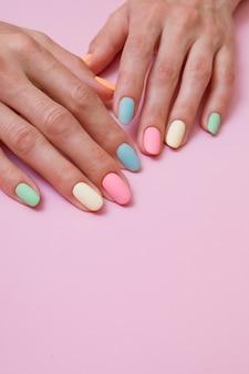 Manicure colorata opaca sulle mani femminili su una superficie rosa
