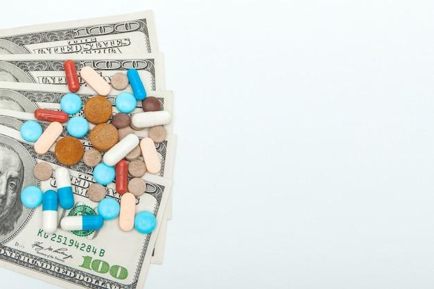 Pillole medicinali colorate e dollari americani su uno sfondo bianco.