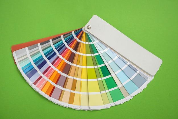 Nuovi modelli di ventagli colorati con colori diversi per la scelta del design si trovano su sfondo verde. idea di design