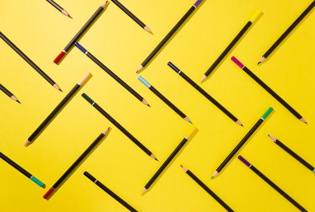 Le matite colorate sono disposte graficamente sul giallo