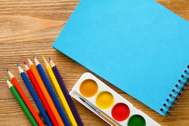 Matite colorate, un blocco da disegno in bianco e acquerelli su un tavolo di legno.