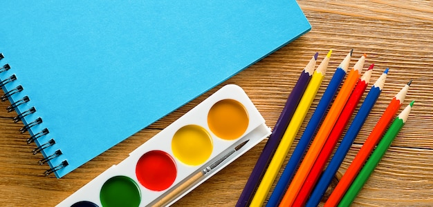 Matite colorate, un blocco da disegno in bianco e acquerelli sulla tavola di legno.