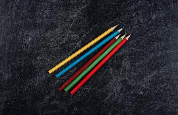 Matite colorate su uno sfondo di lavagna. di nuovo a scuola. vista dall'alto.