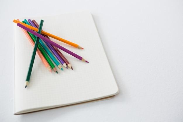 Matite colorate tenute sul libro
