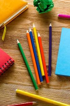 Matite colorate e pennarelli, cuscinetti da disegno su un tavolo di legno.