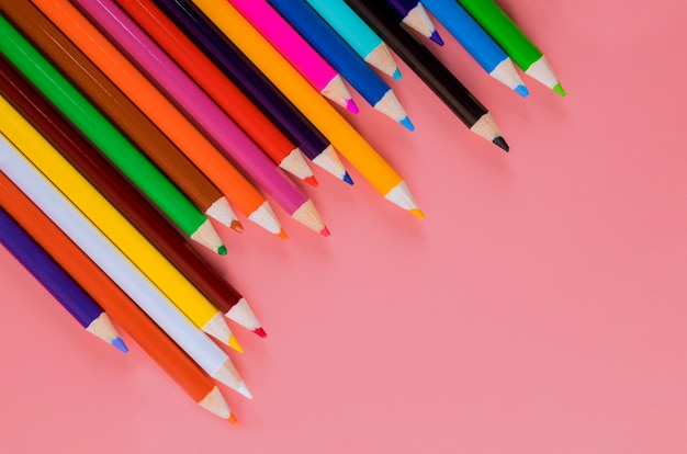 Matite colorate su sfondo rosa per arte e scuola