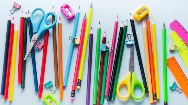 Matite colorate, forbici, quaderno, righello, penna, gomma, temperamatite e altro in vetro. cancelleria per ufficio e scuola sul tavolo azzurro. concetto di ritorno a scuola. vista dall'alto.