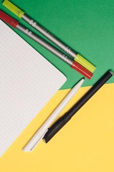 Penne e pennarelli colorati su uno sfondo luminoso e un blocco note bianco sul tavolo