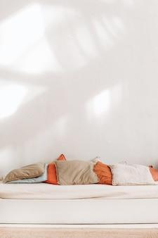 Cuscini colorati in materiali ecologici naturali sul letto beige in un design interno leggero