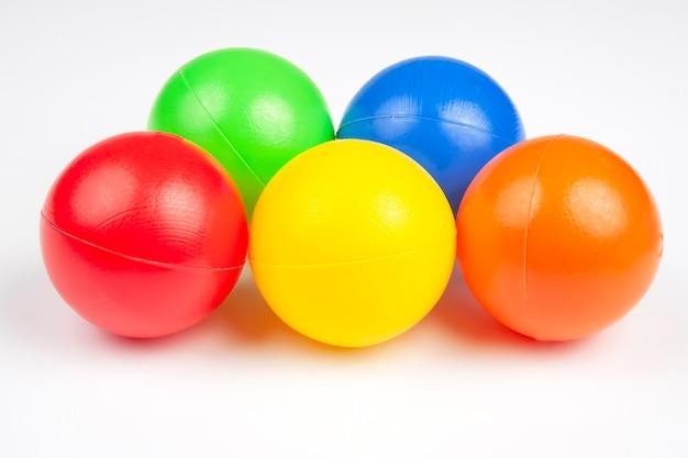 Sfere di plastica colorate su sfondo bianco. oggetti per il tempo libero e il gioco. oggetti rotondi