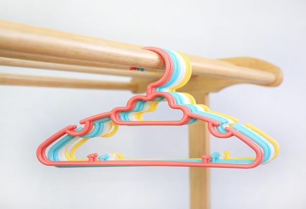 Appendiabiti in plastica colorata su stendibiancheria in legno su sfondo bianco