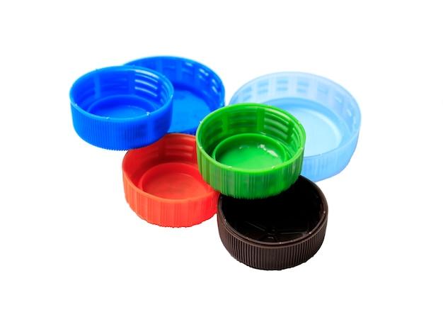 Coperchi in plastica colorati isolati su sfondo bianco. riciclaggio della plastica