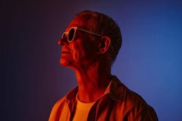 Ritratto colorato di un uomo anziano moderno che indossa occhiali da sole in rosso e blu, copia spazio