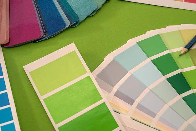 Campioni colorati di modelli di ventagli con quadrati di matite colorate giacciono su uno sfondo verde