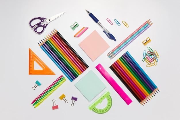 Materiale scolastico colorato per l'apprendimento su bianco, piatto