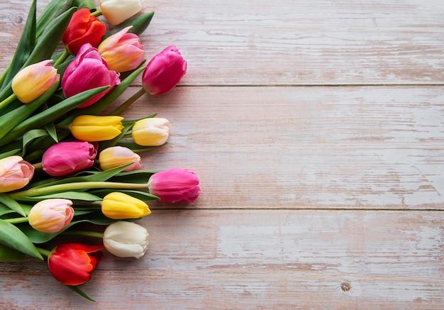 Tulipani colorati primaverili su uno sfondo di legno