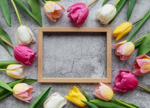 Tulipani colorati primaverili e cornice in legno su una superficie di cemento