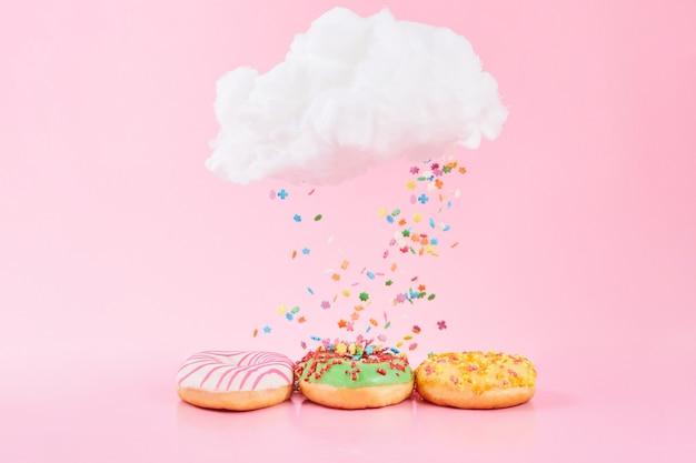 Granelli colorati cadono dalla nuvola. ciambelle assortite glassate, rosa satinato e spruzza su sfondo rosa.
