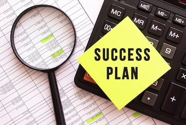 Sulla calcolatrice si trova un adesivo colorato con il testo piano di successo. concetto finanziario.