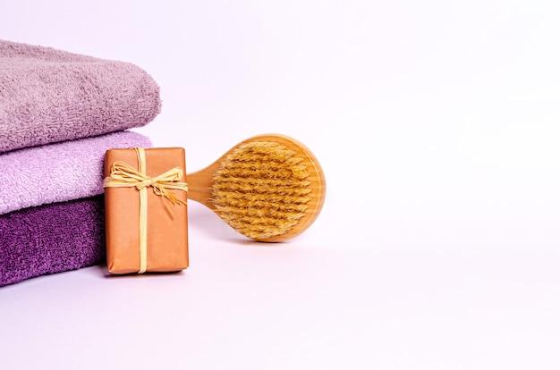 Asciugamani colorati in spugna, sapone e spazzola per massaggi su sfondo bianco. una pila di asciugamani di cotone con spazio per il testo. avvicinamento.
