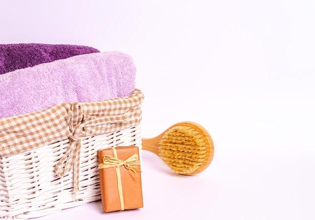 Asciugamani di spugna colorati in un cesto, una spazzola da massaggio in legno, sapone su sfondo bianco. lay piatto, copia spazio. il concetto di procedure termali, cura del corpo. avvicinamento