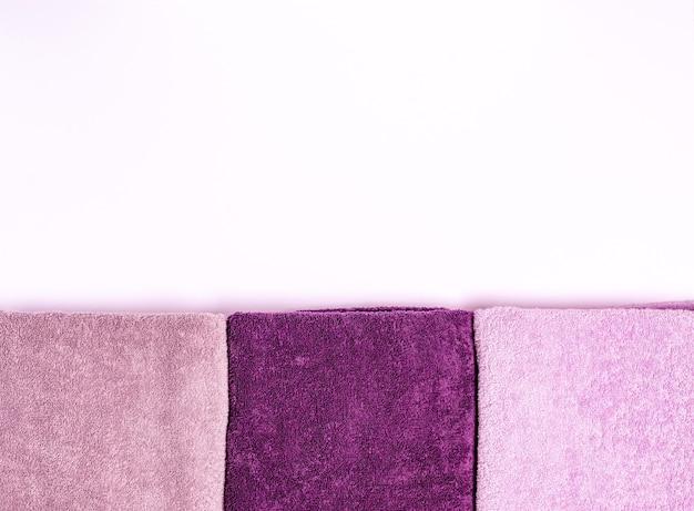 Asciugamani di spugna colorati su sfondo bianco. disposizione piatta, copia spazio, posto per il testo. il concetto di cura del corpo, igiene personale. vista dall'alto