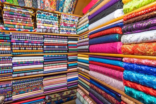 Tessili o tessuti colorati in un mercato asiatico di strada, mensole con rotoli di tessuto e tessuti