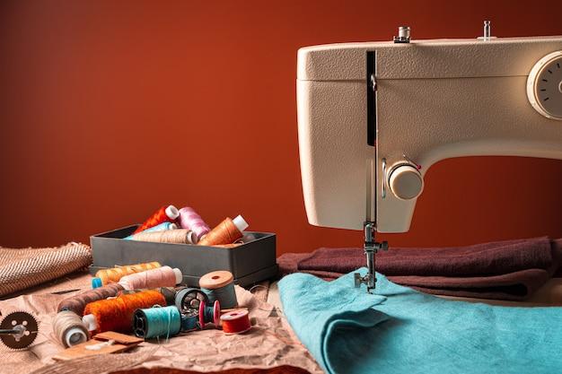 Fili colorati, tessuti e una macchina da cucire su fondo marrone.