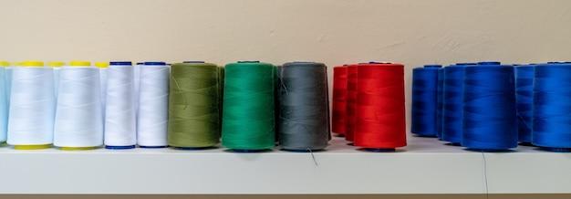 Fili colorati per la macchina da cucire sullo scaffale