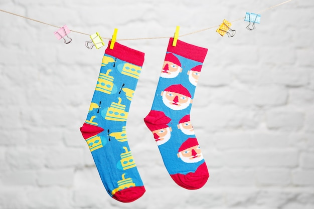 Calzini casual invernali colorati appesi a un filo e legati con un panno su uno sfondo di mattoni bianchi.
