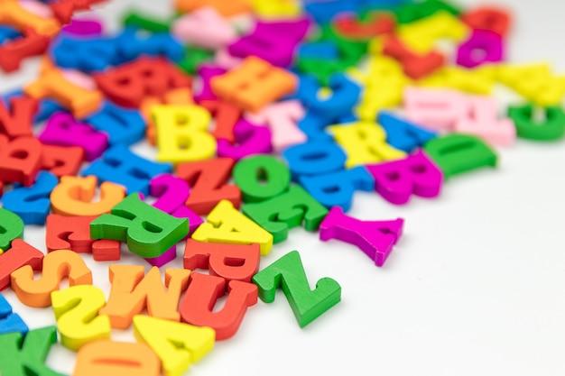 Lettere in legno colorate dell'alfabeto inglese su sfondo bianco, spazio copia