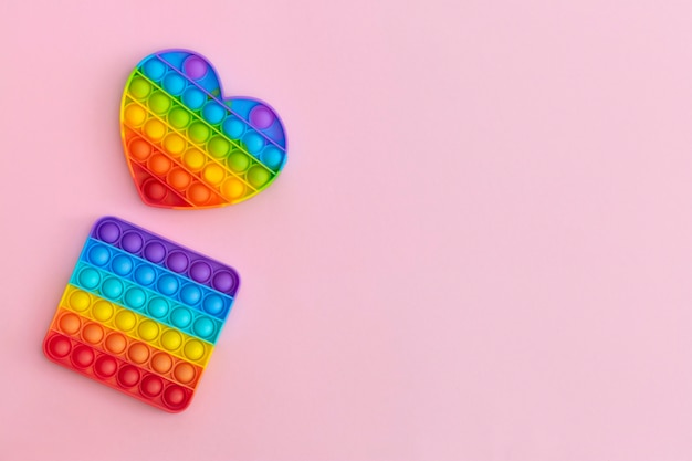 Giocattoli colorati antistress pop it sensoriali per bambini su sfondo rosa