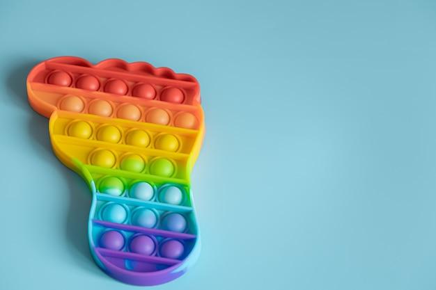 Colorato antistress sensoriale pop it gioca a forma di piede su sfondo blu.