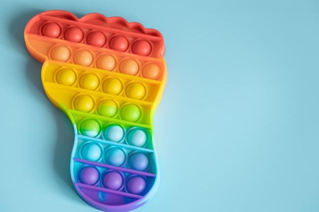 Pop sensoriale antistress colorato gioca a forma di piede su superficie blu