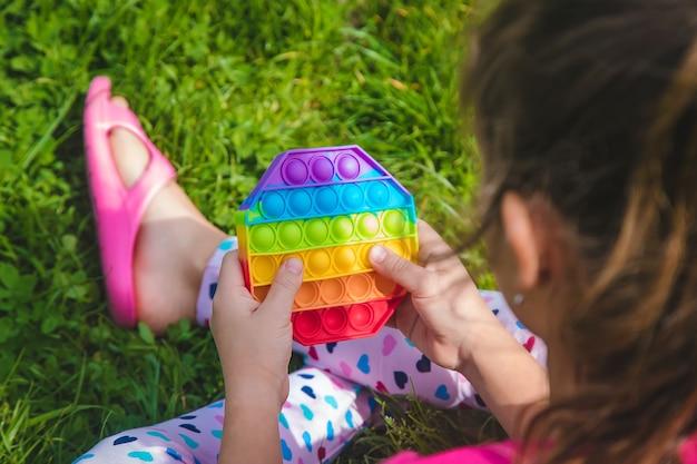Colorato giocattolo sensoriale antistress agitarsi spingilo pop nelle mani del bambino. messa a fuoco selettiva. natura. Foto Premium
