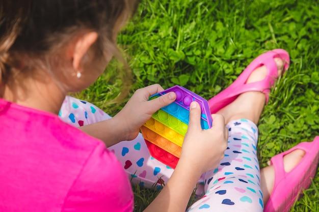Colorato giocattolo sensoriale antistress agitarsi spingilo pop nelle mani del bambino. messa a fuoco selettiva. natura.
