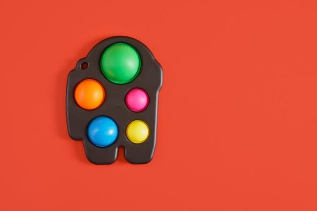 Giocattolo sensoriale antistress colorato fidget push pop it o semplice fossetta su sfondo rosso copia spazio vista dall'alto