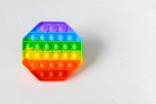Giocattolo sensoriale antistress colorato pop it su sfondo bianco con spazio di copia